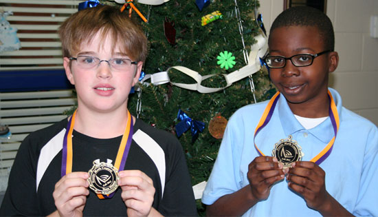 Miles Burgess and Nnume Nwankwo show the awards earned in the Noetic Math competition.