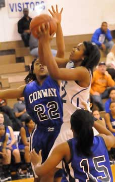 Bryant's Taneasha Rhode goes up for a shot as she's contested by Conway's Enjinae Chambers (22). (Photo by Kevin Nagle)