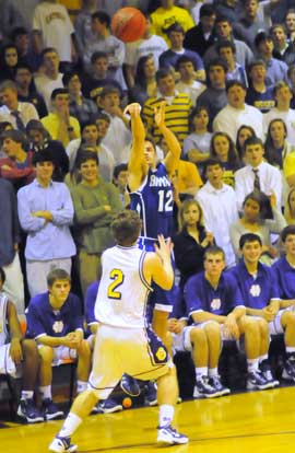 Brantley Cozart (12) launches a 3-pointer over Catholic's Mitchell Luther. (Photo by Kevin Nagle)