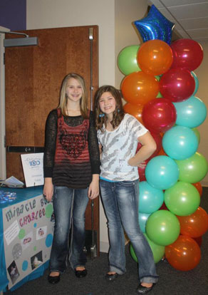 Riley Hill and Elizabeth Palmer in front of the donation table set up at their birthday party at The Center at Bishop Park.