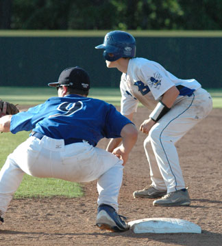 Trevor Ezell leads off first as Conway's Reid Blaylock (9) holds him. (Photo by Kevin Nagle)