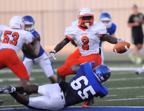 Bryant's Kordell Boykins (65) latches onto Little Rock Hall running back Tony Glover. (Photo by Kevin Nagle)