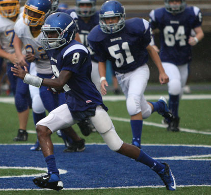 Bryant Blue quarterback Desmond Duckworth turns upfield in front of teammate Kale Kimbroth (51). (Photo by Rick Nation)