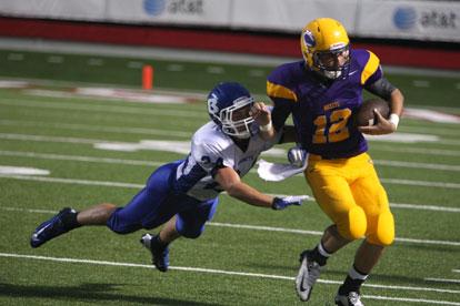 Linebacker Bryce Denker (24) hauls down Catholic quarterback Zac Pinter. (Photo by Rick Nation)