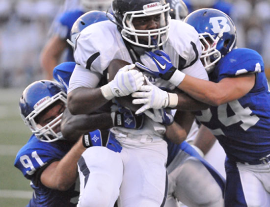 Bryant's Tim Kelly (91) and Bryce Denker (24) latch onto a Conway running back. (Photo by Kevin Nagle)