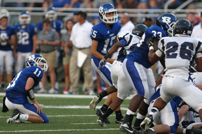 Josh Lowery (15) watches his kick head toward the uprights out of the hold of Austin Vail (11). (Photo by Rick Nation)