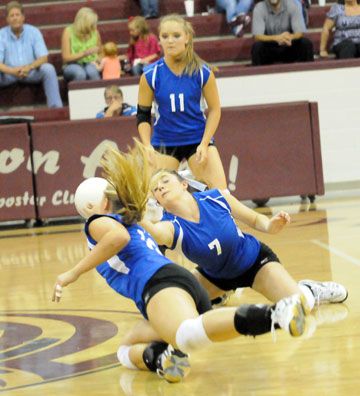 Courtney Davidson (7) and McKenzie Rice dive for a dig in front of teammate Hannah Rice (11). (Photo by Kevin Nagle)