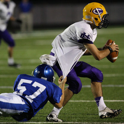 Bryant's Nick Gatlin (57) hangs on to Catholic quarterback Andre Sale. (Photo by Rick Nation)