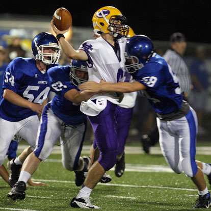 Bryant's Jacob Hall (58), Austin Blacklaw (69) and Walker Brown (54) descent on Catholic quarterback Andre Sale. (Photo by Rick Nation)