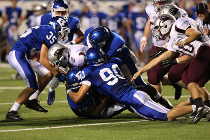 Justin Hollingshead (90), Tyree Reese (33) and Jake Johnson (35) help haul down Terek Beaugard. (Photo by Rick Nation)