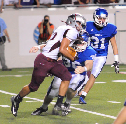 Austin May (36) hits Benton quarterback Terek Beaugard as Bryant's Stoney Stevens (31) closes in. (Photo by Kevin Nagle)