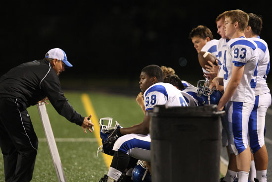Offensive line coach Kirk Bock instructs Cameron Murray (98), Ethan Burnett (93) and the rest of the linemen while the Hornets were on defense Thursday night. (Photo by Rick Nation)