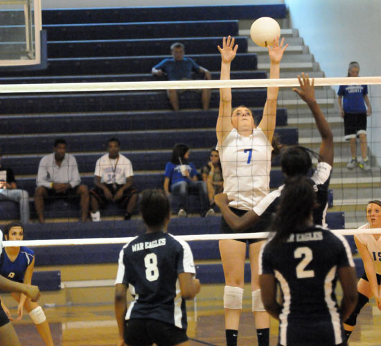 Courtney Davidson (7) goes high to make a block. (Photo by Kevin Nagle)
