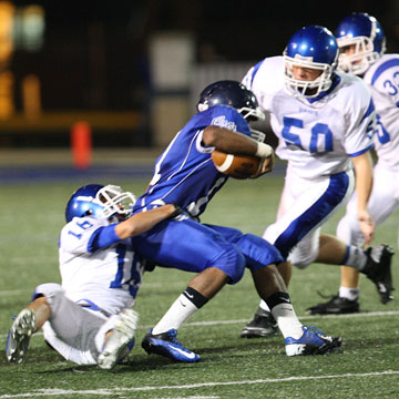 Nick Hardin (16) hauls down Conway's Cris Cotton as help arrives from Austin Fason. (Photo by Rick Nation)