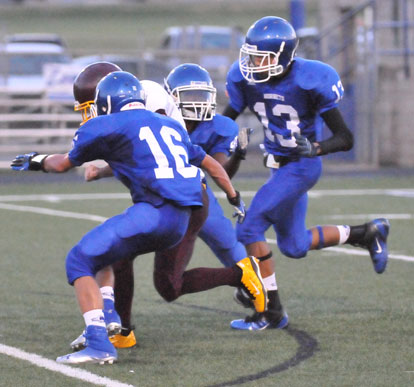 Nick Hardin (16) and Jaelyn Jones (13) join a teammate on a tackle. (Photo by Kevin Nagle)