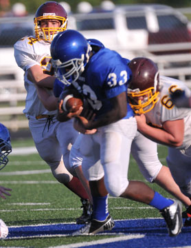 Cameron Coleman (33) fights for yardage. (Photo by Kevin Nagle)
