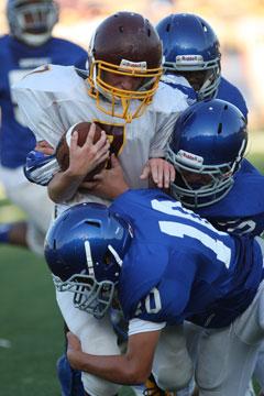Austin Kelly (10) and a pair of teammates bring down Lake Hamilton's Jacob Graves. (Photo by Rick Nation)