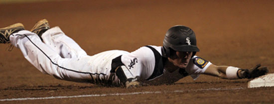 Connor Tatum dives into third at the end of his clutch three-run triple. (Photo by Rick Nation)