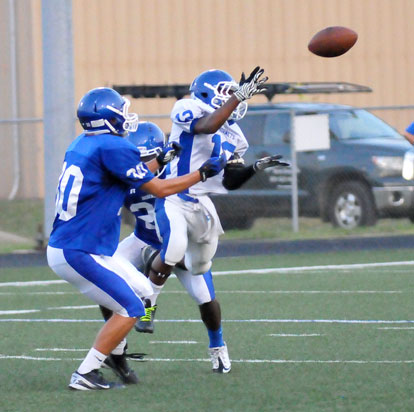 Sophomore Najee Hunt (12) goes up for a pass in front of Dillon Daniels (30). (Photo by Kevin Nagle)