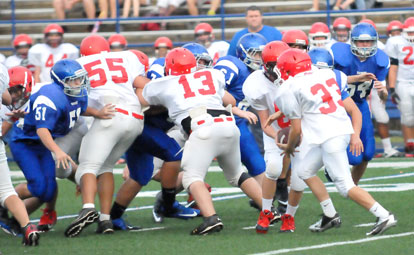 Bryant Blue defenders Logan Rich (51), Brandon Hoover (61) and Cole Campbell (54) and their teammates try to get some penetration against the Cabot North offensive line as quarterback Rail Gilliam hands to Noah Sorrell (33). (Photo by Kevin Nagle)
