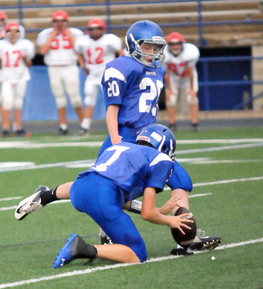 Luke Welch boots an extra point out of the hold of Cameron Vail. (Photo by Kevin Nagle)