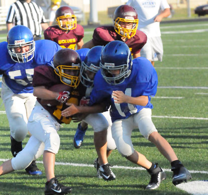 A pair of Bryant White players including Coby Greiner (11) stop a Lake Hamilton ball carrier. (Photo by Kevin Nagle)