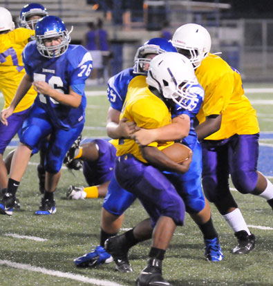 Ryan Harris (75) wraps up a Dunbar ball carrier as Joe Wyllia (76) moves in to help out. (Photo by Kevin Nagle)