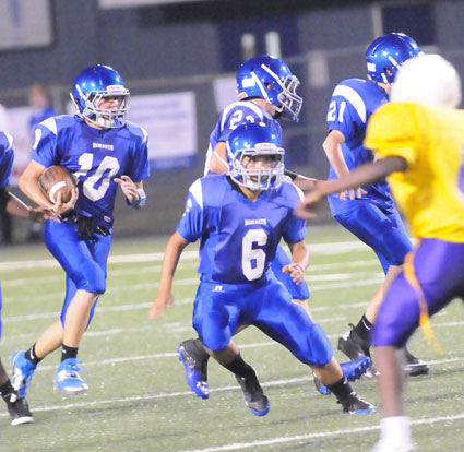 Sarah Evans (6), Parker Littleton (22) and Luke Curtis (21) lead Mike Jones (10) on a kickoff return during Tuesday's game. (Photo by Kevin Nagle)