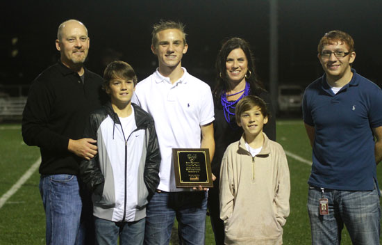 Charlie Terry, along with family members, proudly shows his September Athlete of the Month plaque, presented by Sykes representative Justin Robinson.