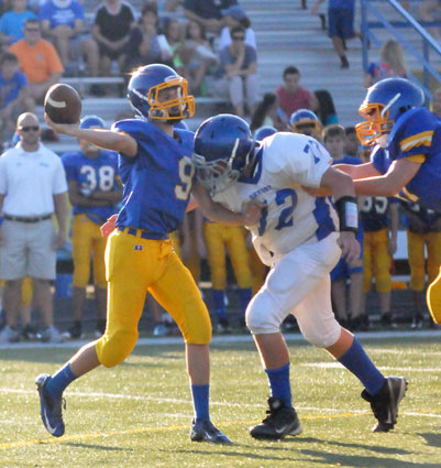 Bryce Thomas (72) pressures Lakeside quarterback Adam Saveall (9) despite being held. (Photo by Kevin Nagle)