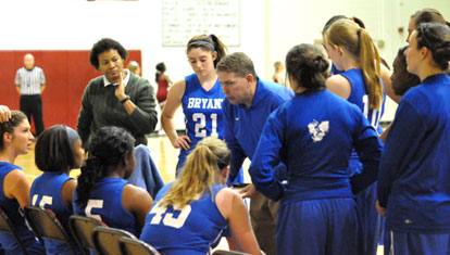 Bryant head coach Brad Matthews and assistant Trina Williams visit the Lady Hornets during a timeout. (Photo by Kevin Nagle)