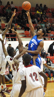 K.J. Hill (5) goes high for a shot over taller Texarkana defenders inside. (Photo by Kevin Nagle)