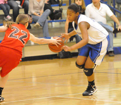 Bryant's Deja Rayford (right) tries to dribble around a Cabot South defender. (Photo by Kevin Nagle)