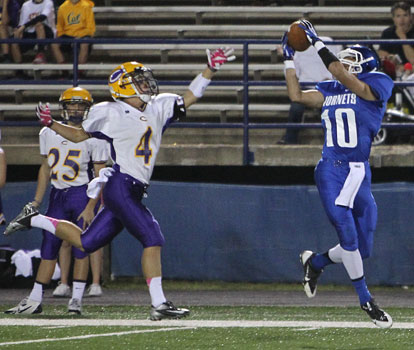 Austin Kelly (10) grabs a pass beyond the reach of Catholic's Joseph Bilger. (Photo by Rick Nation)