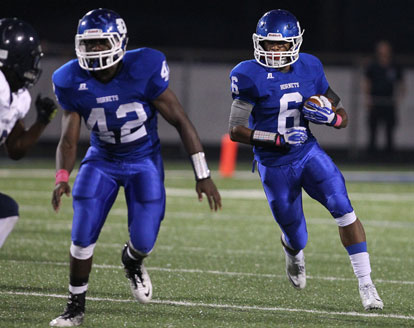 Demaja Price (42) escorts Brendan Young (6) up the field. (Photo by Rick Nation)