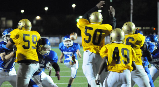 Chase Kincaid kicks an extra point over Central's Terry Humphrey (50). (Photo by Kevin Nagle)