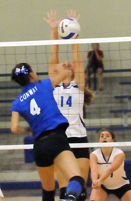 Riley Hill (14) reaches high for a block. (Photo by Kevin Nagle)