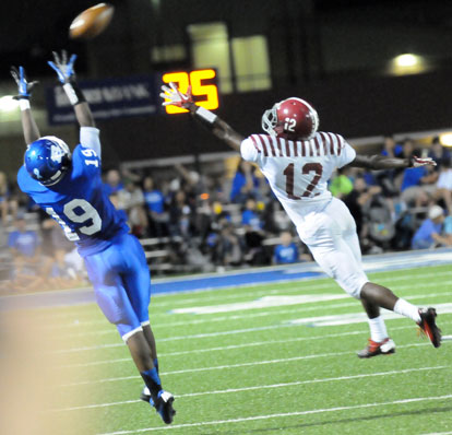 Bryant's Kylon Boyle (19) reaches high for a pass beyond the reach of Pine Bluff's Jayshon Williams (12). (Photo by Kevin Nagle)