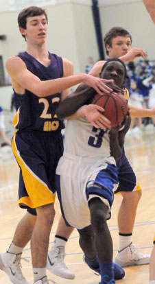 Calvin Allen (3) fights his way to the basket while being fouled by Catholic's John David Falcon (22). (Photo by Kevin Nagle)