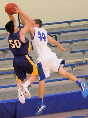 Bryant's Trey Ashmore (44) blocks a shot by Catholic's Josh Neuman. (Photo by Kevin Nagle)