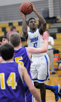 Bryant's Cedarrian Crosby (12) twists to get a shot up over Catholic's William Hancock (5). (Photo by Kevin Nagle)