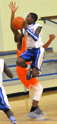 Calvin Allen double clutches as he goes to the basket past a taller Ridge Road defender. (Photo by Kevin Nagle)
