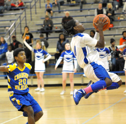 Simeon Watson drives goes up for a shot in front of North Little Rock's Rokar Williams. (Photo by Kevin Nagle)