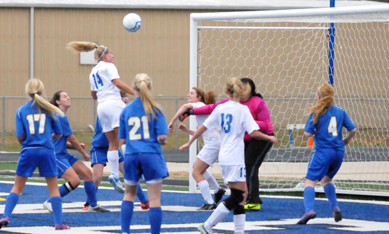 Jacie McMahan heads the ball toward the goal in a crowd. (Photo by Kevin Nagle)