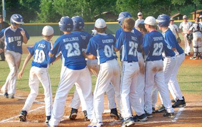 Jacob Coppock is greeted by his teammates after belting a grand slam in the championship game.