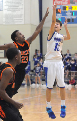 Garrett Cowart launches a shot beyond the reach of Malvern's Jacquez Lock (23). (Photo by Kevin Nagle)
