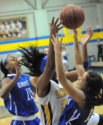 Jakerea Otey (10) and Maddie Baxter battle Sheridan's Kadesha Cooper for a rebound. (Photo by Kevin Nagle)