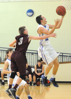 Tristan Calhoun lays up a shot in front of Benton's Graham Chenault (3). (Photo by Kevin Nagle)