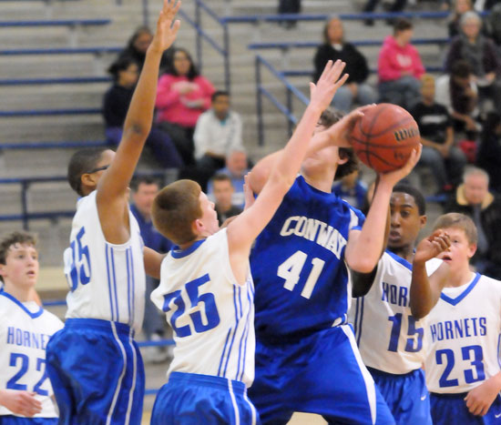 Brandon Shirlee (35) and Luke Curtis (25) challenge a Conway White shooter in the lane. (Photo by Kevin Nagle)