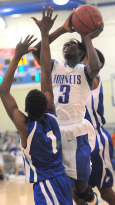 Calvin Allen (3) goes up for a shot between two defenders. (Photo by Kevin Nagle)